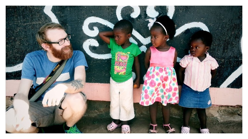Andy, being sized-up by three youngsters outside the community care centre at Hlomelikusasa